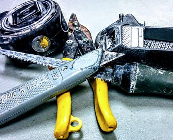 Photo of various drywall tools including a utility knife, keyhole saw, tinsnips, measuring tape, and chalkbox
