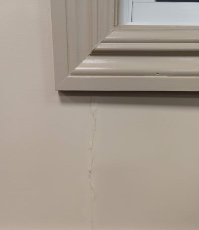 Drywall crack above long opening where beam distributes weight