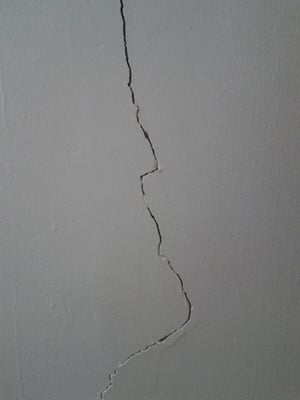Picture of a large crack in a plaster wall