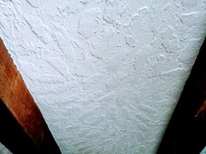 Picture of a hawk and trowel drywall texture next to large wooden beams applied with thick drywall compound