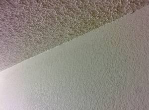 Angled photo of popcorn texture on the ceiling and knockdown on the walls