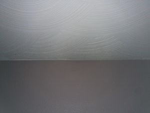 Photo of swirl drywall texture on the ceiling and orange peel texture on the wall